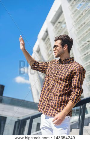 Hello. Stylish young man is standing on street. He is waving arm and looking forward with confidence