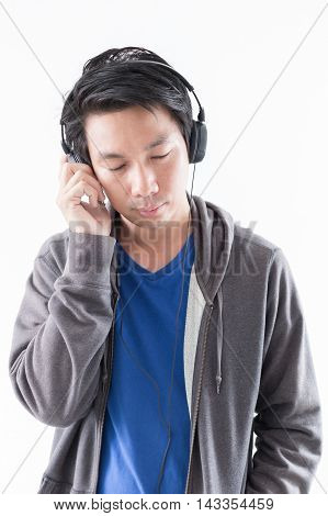 Young man listening to music with headphone on white background