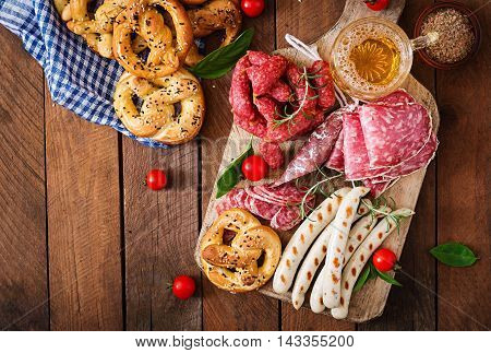 Glass Of Beer, Pretzels And Various Sausages On Wooden Background. Oktoberfest. Top View