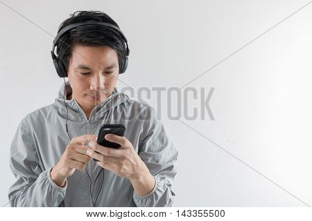 Young man listening to music with smartphone on white background