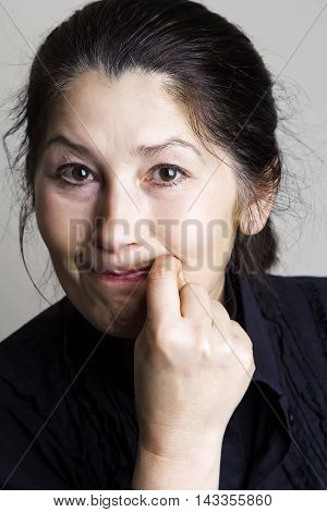 Attractive woman shows a gesture of silence, or mouth shut