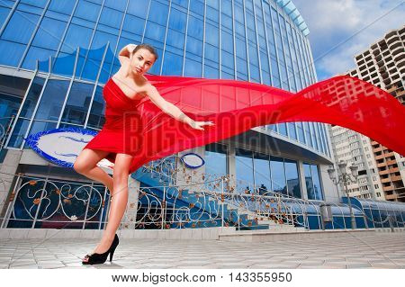 Young Beautiful Girl With The Red Flying Fabric In The City