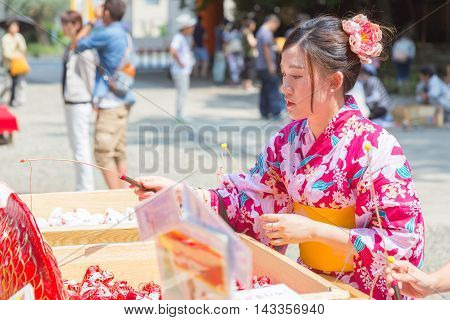 KAWAGOE JAPAN - 20 JULY 2016 - Japanese woman in yugata traditional japanese dress try her luck by baiting lucky fortune paper fish form the piles at Hikawa Shrine in Kawagoe town Japan on July 20 2016.