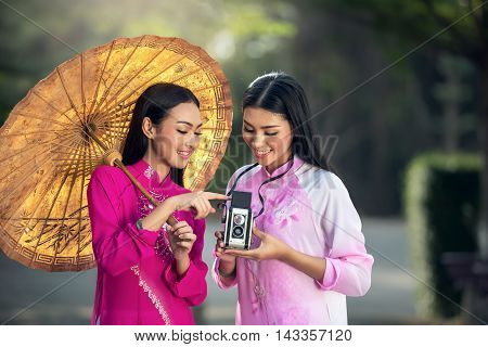 Portrait of Vietnamese girl traditional dress Ao dai is famous traditional costume for woman in Vietnam with vintage camera