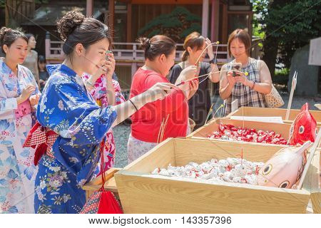 KAWAGOE JAPAN - 20 JULY 2016 - Japanese and Asian tourists try their luck by baiting lucky fortune paper fish form the piles at Hikawa Shrine in Kawagoe town Japan on July 20 2016.