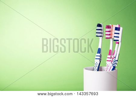 Various toothbrushes in white cup on light green background with copy space on the left side.