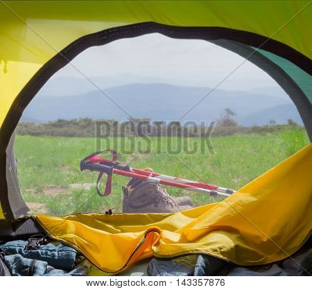 View to the mountains from the hiking tent through the open tent entrance and closed mosquito net
