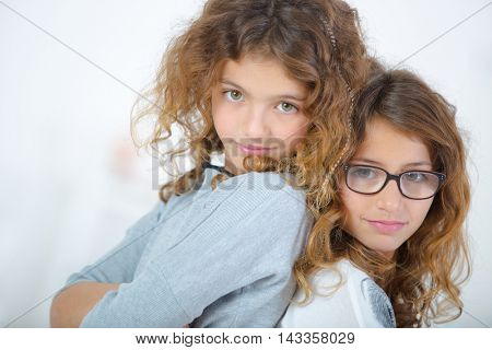 Two young girls stood back to back