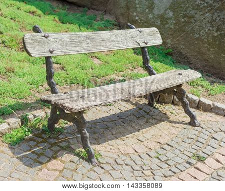 Garden bench with old wooden planks in the park in summer day
