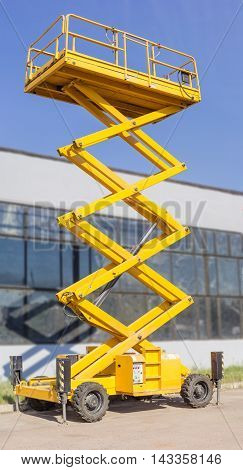 Mobile aerial work platform - yellow scissor hydraulic self propelled lift against the backdrop of an industrial building