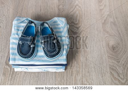 Folded Blue And White Bodysuit With Shoes On It  Grey Wooden Background. Diaper For Newborn Boy. Sta