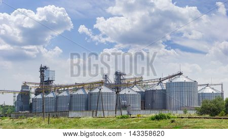 Grain storage system with corrugated steel storage bins and grain distribution system on the background of sky with clouds