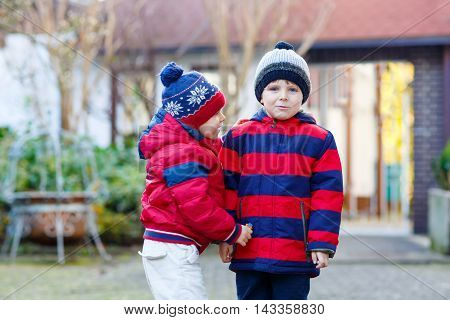 Two little kids boys, friends holding hands and hugging. Adorable siblings in bright colorful clothes. Happy children outdoors, winter or autumn.
