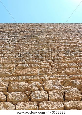 Old quarry stone wall with low angle view and blue sky.
