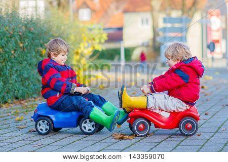 Two little kids boys in colorful clothes and rain boots driving toy cars and making competition, outdoors. Active leisure for children on autumn day