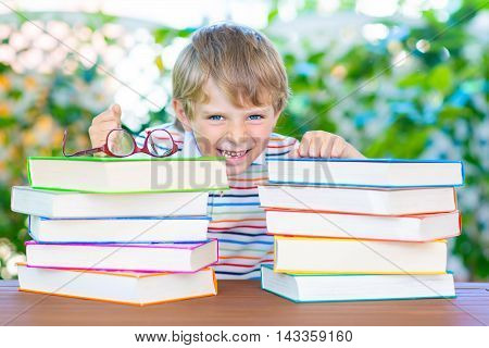 Happy little kid boy with glasses and stack of colorful books. Funny child and student is back to school and is excited of reading on warm day.