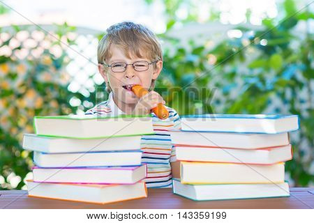Happy little kid boy with glasses and stack of colorful books eating carrot as healthy snack. Funny child and student is back to school and is excited of reading on warm day.