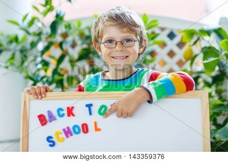 Cute beautiful little kid boy with glasses and white board with letters. Child and student is back to school and happy about begin of lessons.