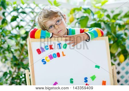 Frustrated and disappointed little kid boy with glasses and white board with letters. Child and student is back to school and sad about begin of lessons.