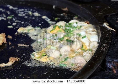 Asian style cooking soft oyster omelette in big black pan