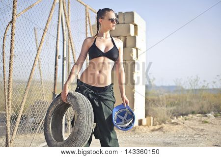 Beautiful worker holding a safety helmet and a wheel