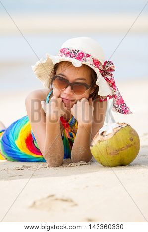 Young woman in swimsuit with coconut cocktail on the beach Bali