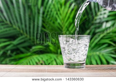Drinking water is poured into a glass. Glass of water on nature background.