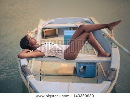 Beautiful woman in white swimsuit relaxing on a little boat