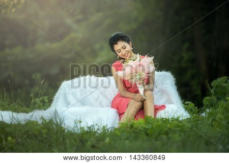 Sofa Woman relaxing enjoying luxury lifestyle outdoor day dreaming and looking bouquet smiling cheerful