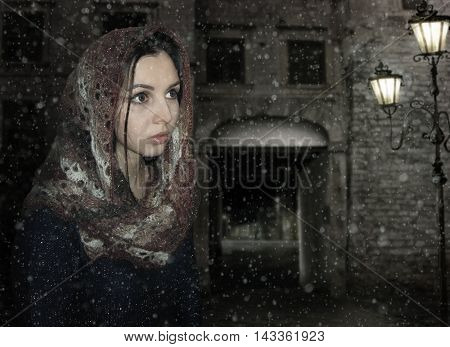 There is a face of a girl in a scarf on the background of night street.