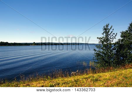 Blue Lake and Sky seen from the Grassy Shore on a Fine Summer Day (Photo taken on Kizhi, Russia)