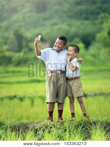 Two young boys taking selfie with mobile phone