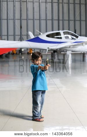 7 years old Asian boy playing toy in hangar with airplane background