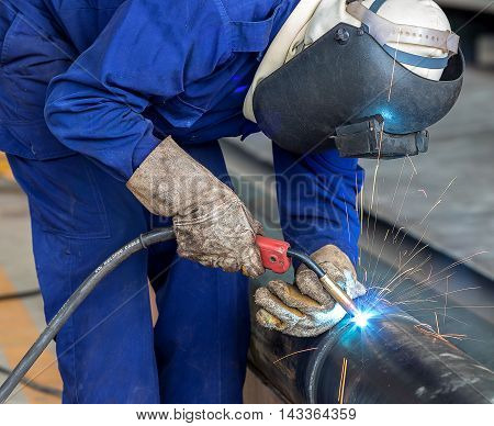 Industrial welding worker at the factory welding steel pipe with safety protective mask