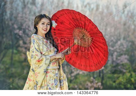 Attractive asian woman wearing traditional Japanese Kimono with red umbrella