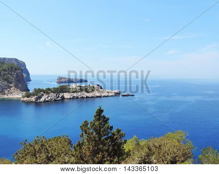 Panoramic viewpoint over the sea with islands and pine trees.