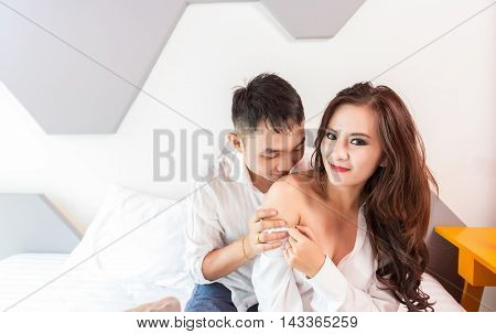 a attractive young couple is kissing in their bed at home