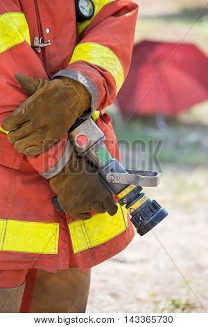 fireman hand in work suit and glove hold fire branch in standby position