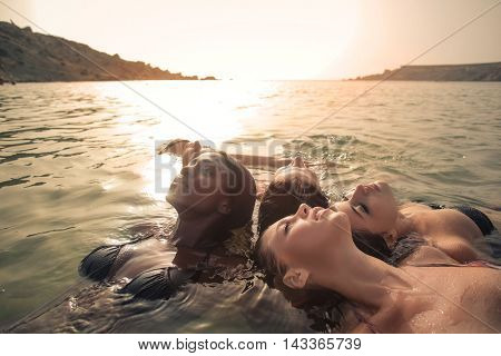Relaxed friends floating in the water