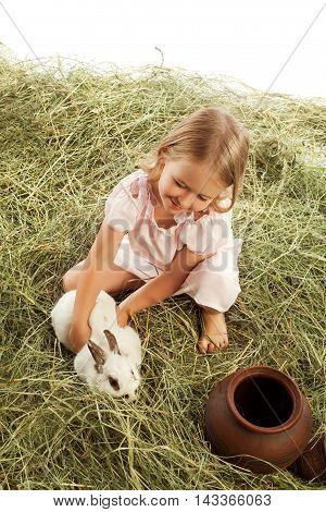 Cute little girl is playing in the hayloft with rabbit-Isolated on white background