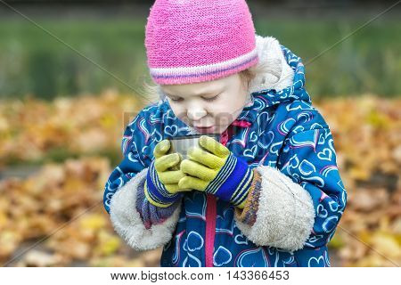 Close-up autumn portrait of little girl is drinking hot beverage from stainless thermos flask cup