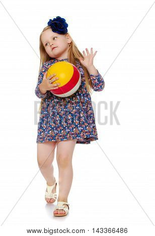 Shy little girl with long blond hair below the shoulders, which are attached to a large blue flower . In a short blue dress playing with a ball - Isolated on white background