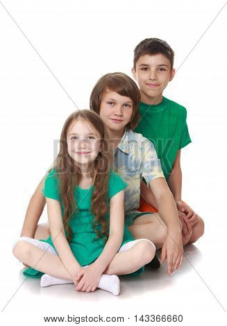 Two brothers and a sister sitting on the floor to each other, and posing for the camera. Portrait of a child where there were 3 people - Isolated on white background