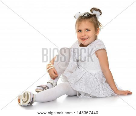 Smiling little Princess in a magnificent white dress. Girl sitting on the floor clasping his hand knee . Looking at the camera a happy look - Isolated on white background