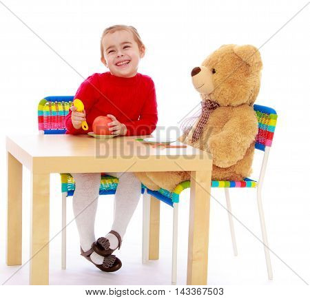 Cute little girl in a red dress in a Montessori kindergarten. Girl sitting at the table with a large Teddy bear and feeds him an Apple - Isolated on white background