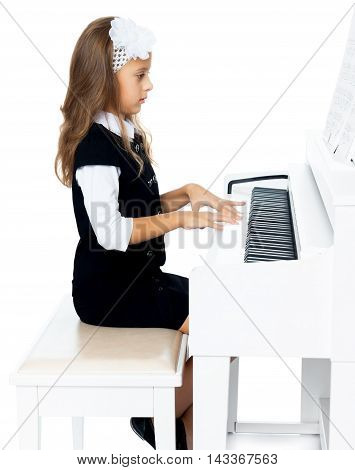 Beautiful little girl in the music school, learning to play the piano . the girl looks directly on the keys - Isolated on white background