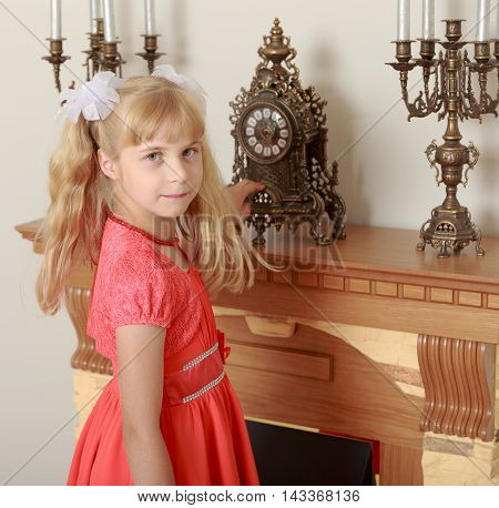 Beautiful little girl in a red dress staring at the clock standing on the mantelpiece