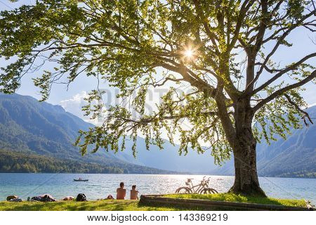 Active sporty couple relaxing on lake beach after active day of cycling enjoying beautiful nature around lake Bohinj, Slovenia.