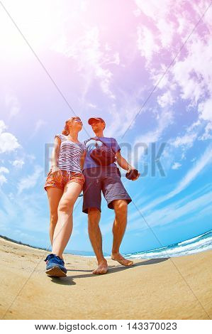 couple walking on the sunny beach at the sunrise. Area Chania city, Crete, Greece.