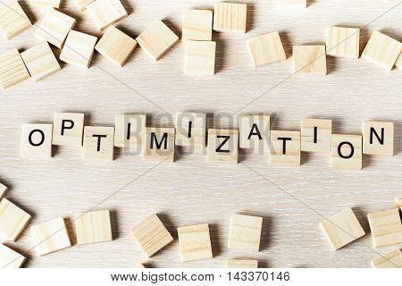 Optinization word written on wood block. Wooden abc.